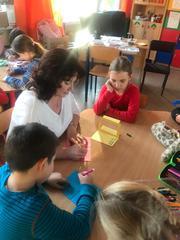 Uczniowie wspólnie z nauczycielką wykonują upominki dla dziadków.