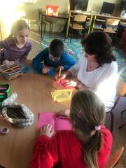 Pani pomaga dzieciom wypisać życzenia na laurce.