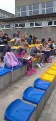 Uczniowie siedzą na trybunach i rysują zawodników w czasie meczu.