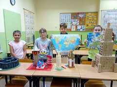 Uczniowie stoją za pracami konkursowymi przedstawiającymi Stonehengo, Centrum Londynu, Wieżę w Pizie, Big Ben i Pałac Kultury. Dwoje uczniów trzyma mapy- świata i Europy.
