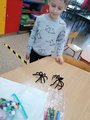Chłopiec ze swoimi pracami: czarnymi pająkami.