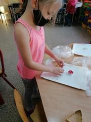 Dziewczynka w maseczce formuje kształt świecznika.