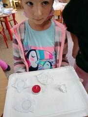 Dziewczynka prezentuje wykonane świeczniki.