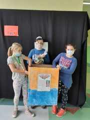 Dzieci trzymające ozdobione pudełko do zbiórki nakrętek