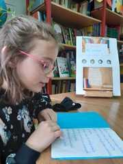 """Alicja czyta książkę """"Luna i jej przygody""""."""