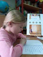 """Laura czyta książkę """"Mały piesek Azorek""""."""
