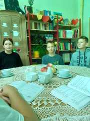 Grupa uczniów czyta Moralność pani Dulskiejw szkolnej bibliotece.jpeg