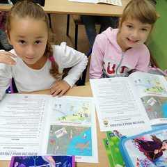 Dziewczynki oglądają otrzymaną książkę.
