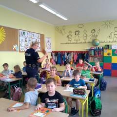Pani policjantka rozdaje dzieciom książeczki.